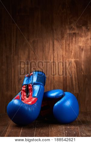 Pair of blue and red boxing gloves on wooden surface against brown wooden wall background. Close-up and vertical photo. Sportive accessories and sportwear. Sportive training and exercise. Healthy lifestyle.