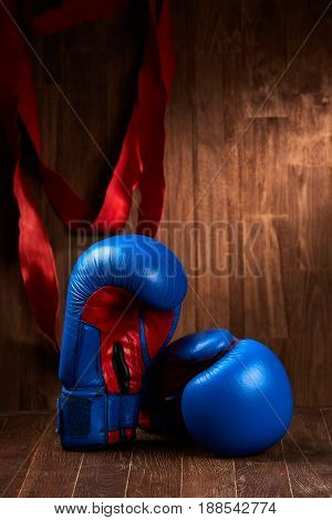 Two blue and red boxing gloves and red bandage on brown plank against wooden wall background. Vertical photo and close-up. Sportwear and spo rtive accessories. Sportive training and exercise. Concept of the active helathy lifestyle.