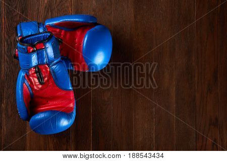 Pair of blue and red boxing gloves lying on the brown wooden table. Sportive and active lifestyle. Close-up horizontal photo. Colorful sportive accessories and sportwear. Sportive exercise and training.