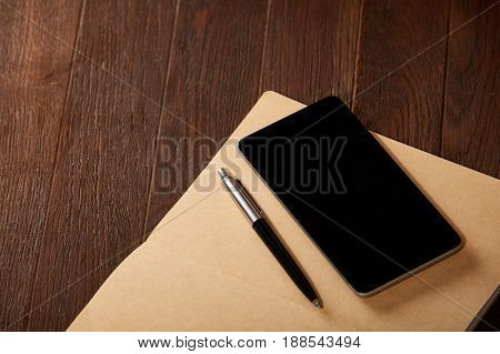 Notebook, telephone and pen on the brown wooden background. Horizontal photo, close-up and top view. Planning every day. Daily affairs. Business or education.