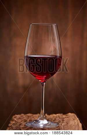 Close-up of crystal half-ful wineglass with red wine standing on wooden stand against wooden background. Luxury lifestyle, celebration and relexation. Natural material and product. Sommelier and tasting. Horizontal photo.