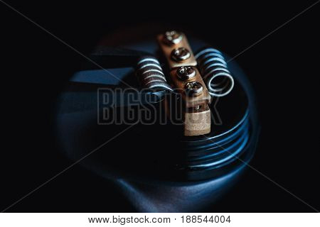 male master installs a coil. Spiral for electronic evaporator and cigarette. Vape, vaping. Firing a coil.Ceramic tongs Burns, styling.