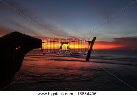 Sunset and ocean through glasses in one hand