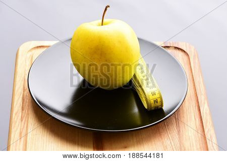 Apple Lying On Shiny Black Ceramic Plate Near Sewing Centimeter