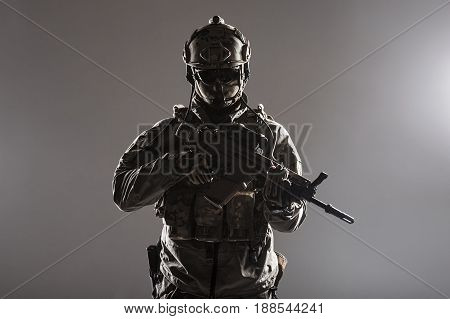 Army soldier in Protective Combat Uniform holding Special Operations Forces Combat Assault Rifle. Studio shot, low key, cropped, black dark background, contour shot