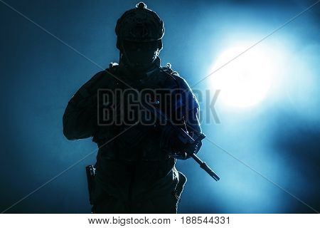 Army soldier in Protective Combat Uniform holding Special Operations Forces Combat Assault Rifle. Studio shot, backlit silhouette