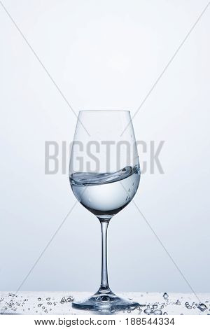 Pure water wave in the wine glass while standing on the glass with water bubbles against light background. Cleaner and useful water. Environmentally friendly product. Care for the environment. Healthy lifestyle.
