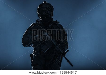 Army soldier in Protective Combat Uniform holding Special Operations Forces Combat Assault Rifle. Studio shot, silhouette