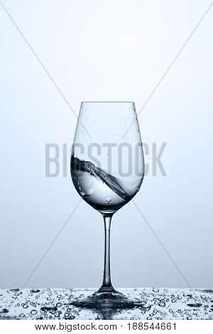 Cleaner and freshness water wave in the wineglass while standing on the glass with water bubbles against light background. Environmentally friendly product. Care for the environment and health. Healthy lifestyle.