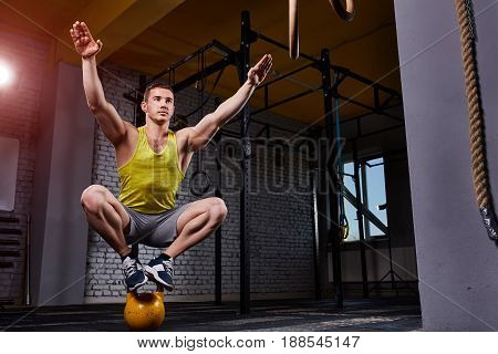 Cross fit fitness man standing and balance on the kettlebells in the gym against brick wall. Sportsman in the sportwear, yellow t-shirt, shorts and sportive shoes. Portrait of happy and smiling athletic man. Healthy lifestyle.