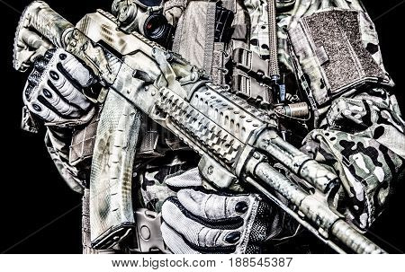 Close-up shot of Kalashnikov rifle automatic weapons in hands of army special forces soldier isolated on black background