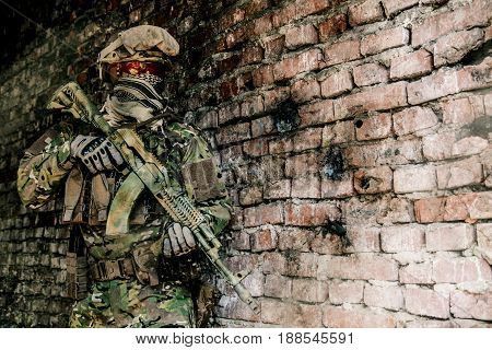 Operator of Russian special operations forces with kalashnikov assault rifle and combat helmet in ruined buliding during military operation in Syria. Bullet holes on the wall