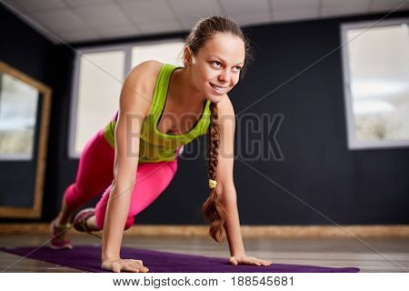Portrait of the young beautiful fitness woman doing plank position indoors at the gym on the violet yoga mat. Sporty woman in the sportwear, green t-shirt, leggings and sportive shoes. Healthy lifestyle.