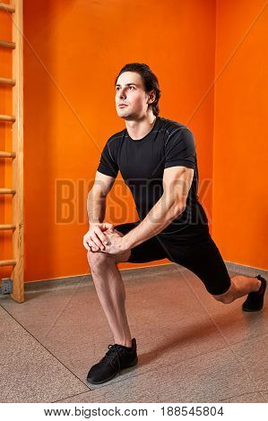 Young sportsman in the black sportwear stretching leg before gym workout against bright orange wall. Athlete man in the t-shirt, shorts and sportive shoes. Healthy lifestyle.