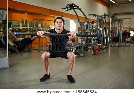 Sporty young man in the black sportwear with barbell flexing muscles in gym. Athlete man in the black t-shirt, shorts and sportive shoes. Energy and power. Healthy lifestyle.