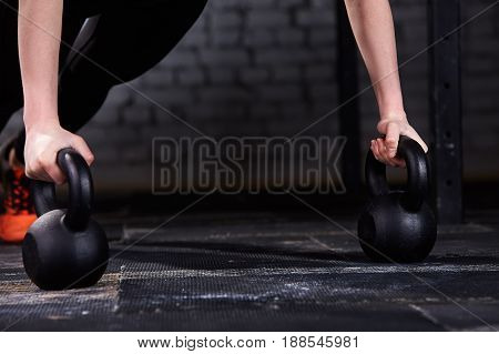 Close-up photo of young athlete woman's hands while doing push ups on kettlebells against brick wall in the gym. Black leggings and orange sporty shoes. Detail of the sporty woman. Healthy lifestyle.