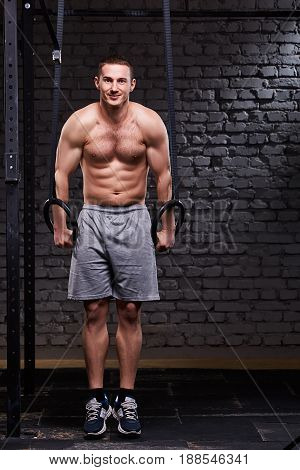 Young athletic man pull ups with gymnastic rings against brick wall at gym. Sportsman in the sportwear, shorts and sportive shoes. Vertical photo. Portrait of the smiling athletic man. Healthy lifestyle.