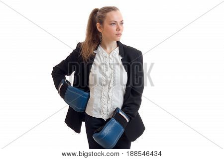 Serious strong blonde business woman in uniform and boxing gloves looking away isolated on white background