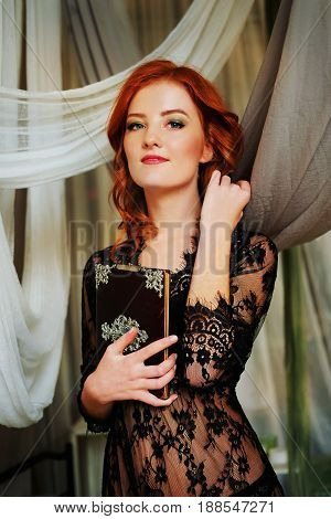 Redhead woman in black lace peignoir on the bed in her bedroom among velvet pillows holding a mysterious black book.