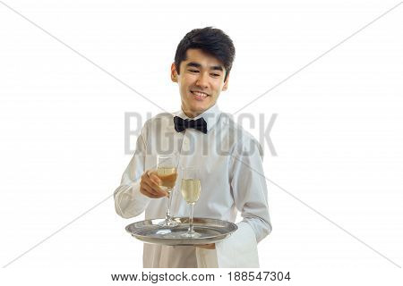 Cheerful man waiter in uniform and bowtie with glasses of white wine on silver tray smiling in studio