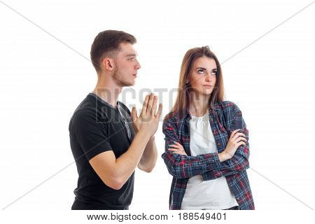a young guy in a t-shirt folded palms together looking at the girl and asks forgiveness isolated on white background