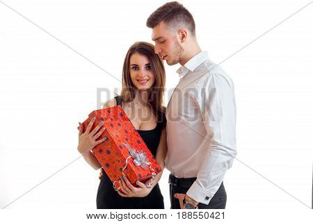 the charming, smiling girl standing next to a guy and holding a big red gift close-up isolated on white background