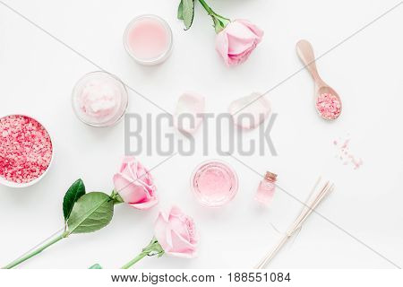 homemade spa with rose cosmetic set, cream, salt and oil on white desk background top view