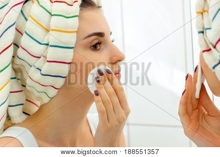 a young girl with a towel on his head wipes face makeup with a cotton disk close-up