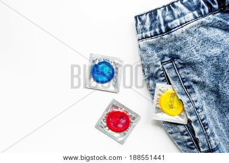 safe sex with condom contraception in jeans pocket on white desk background top view mock-up