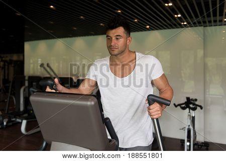 Healthy Athlete Doing Aerobics Elliptical Walker In Gym