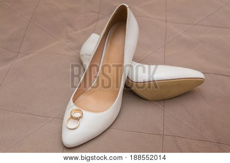gold wedding rings lie on white shoes close up