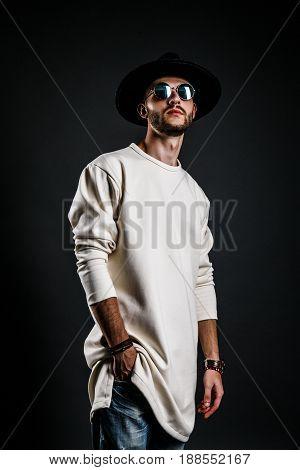 Cool stylish handsome man wearing sunglasses and hat. Studio shot.