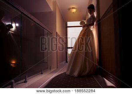 Silhouette portrait of young bride in wedding dress