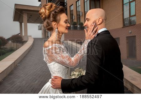 Happy young just merried couple hugging outdoors at raining weather
