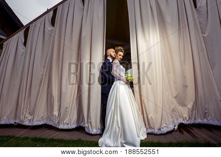 Beautiful young just merried couple hugging on a scene