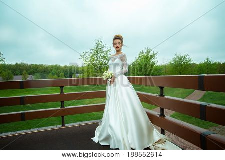 young beautiful bride in wedding dress posing outdoors at raining weather