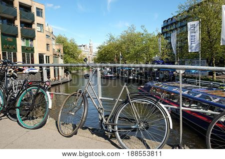 AMSTERDAM NETHERLANDS - MAY 14 2017: Bicycles are parked to the railings of the bridge through the canal
