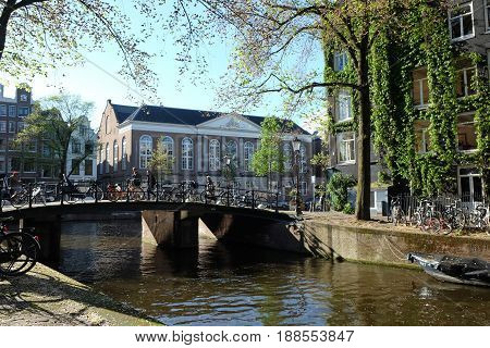 AMSTERDAM NETHERLANDS - MAY 14 2017: View of canal bridge and houses in Amsterdam