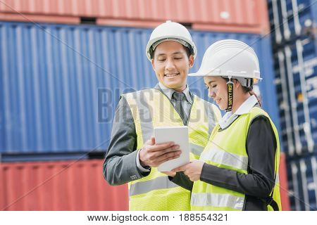 Secretary and businessman in logistic export import industry with shipping cargo container freight in background.
