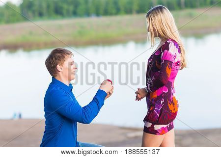 holidays, love, couple, relationship and dating concept - romantic man proposing to a woman on nature.