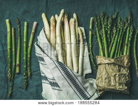 Fresh green and white asparagus in towel over dark grey linen table cloth background, top view, horizontal composition