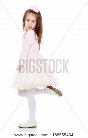 Dressy little girl long blonde hair, beautiful pink dress and a rose in her hair.She turned sideways to the camera and stands on one leg.Isolated on white background.