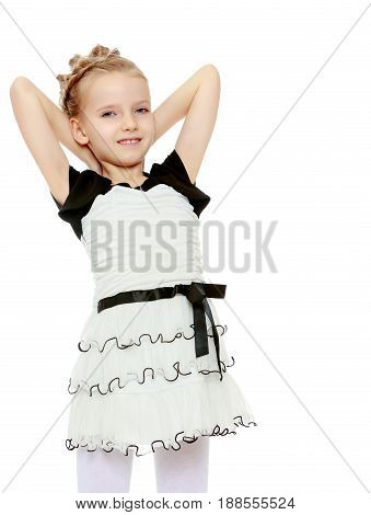 Beautiful little blonde girl dressed in a white short dress with black sleeves and a black belt.The girl slung over the head hands.Close-up.Isolated on white background.