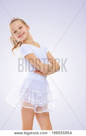 Beautiful little girl gymnast in a white sports suit poses for the camera.