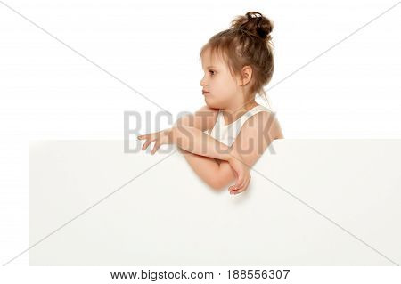 Cute little girl peeking out from behind the white banner.Isolated on white background.