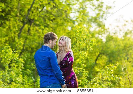 Romantic happy couple in love on nature. Man and woman kissing in summer park