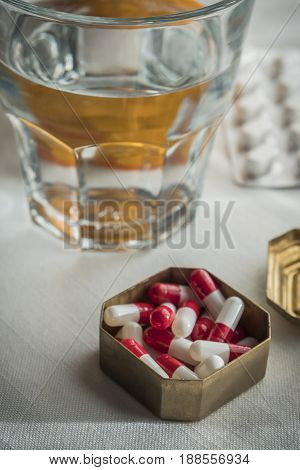 Metallic Pillbox With White And Red Capsules Along With Water Glass