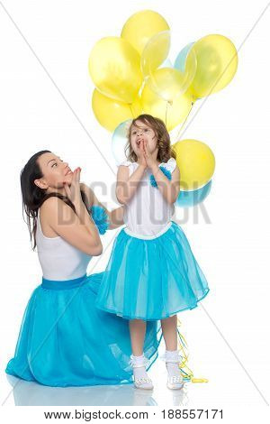 Beautiful mother and daughter in long blue skirts, along with balloons.They rejoice in the holiday.Isolated on white background.