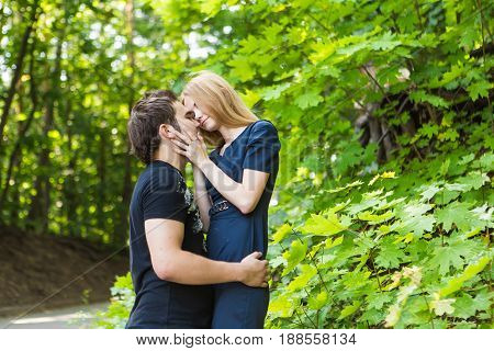 Young couple outdoor portrait. Beautiful pretty girl kissing handsome boy. Sensual photo.