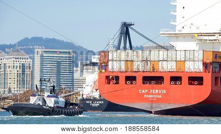 Oakland CA - May 28 2017: Tugboat SANDRA HUGH at the stern of cargo ship CAP JERVIS assisting the vessel to manuever out of the Port of Oakland.